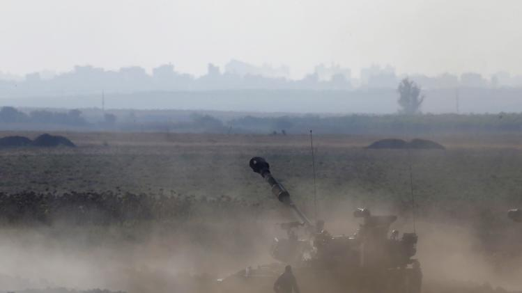 Smoke is seen next to an Israeli mobile artillery unit after it fired towards the Gaza Strip