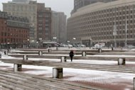 A woman walks across a deserted city hall plaza February 8, 2013 in Boston, Massachusetts. A coming blizzard is expected to bring heavy snow, high winds and coastal flooding, bringing a halt to public transportation, and airport traffic, beginning this afternoon, and into tomorrow.