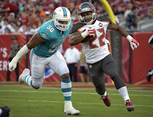 Doug Martin eludes Dolphins DE Olivier Vernon during a first-quarter run Saturday. (AP)