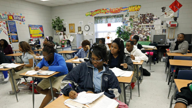 In this Feb. 15, 2013 photograph, Clarksdale High School students delve into the complexities of chemistry equations, in Clarksdale, Miss. Community leaders hope improved education will help stanch a hemorrhaging population. The city's nine public schools may also be the crossroads of Mississippi's education system as state lawmakers are considering a new route, one characterized by charter schools, teacher merit pay, a tougher statewide curriculum, state-paid preschool classes and an intensive focus on reading for young students. (AP Photo/Rogelio V. Solis)