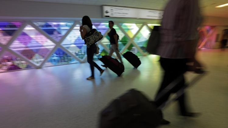 """In this Thursday, Sept. 27, 2012 photo, passengers travel through an airport in Miami. Private researchers, who have analyzed federal data on airline performance, say in a report being released Monday, April 8, 2013, that consumer complaints to the Department of Transportation surged by one-fifth last year even though other measures such as on-time arrivals and mishandled baggage show airlines are doing a better job. """"The way airlines have taken 130-seat airplanes and expanded them to 150 seats to squeeze out more revenue I think is finally catching up with them,"""" says Dean Headley, a business professor at Wichita State University, who has co-written the annual report for 23 years. (AP Photo/Lynne Sladky)"""