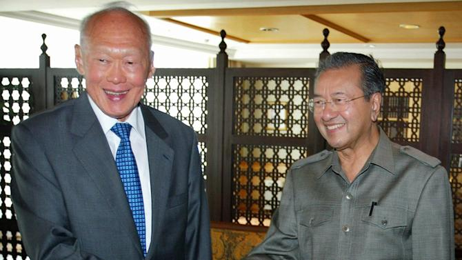 FILE - In this April 27, 2005 file photo, Singapore Minister Mentor Lee Kuan Yew, left, and former Malaysian Prime Minister Mahathir Mohamad shake hands at the latter's office in Putrajaya, outside Kuala Lumpur. Two of Asia's best-known strongmen, Singapore's Lee Kuan Yew and Malaysia's Mahathir Mohamad, had much in common - a streak of authoritarianism, little tolerance for dissent and vision that changed the face of their countries. But friends they were not, and the two rarely saw eye to eye. (AP Photo/Bazuki Muhammad, File)
