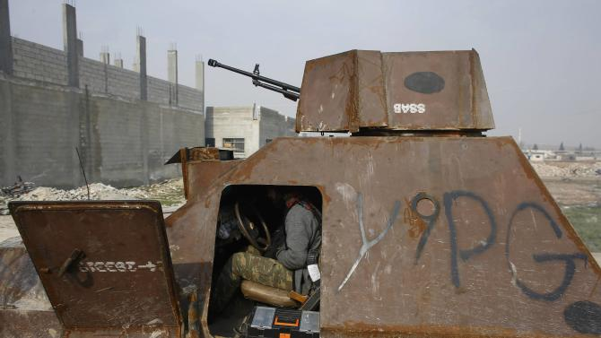 A fighter of the Kurdish People's Protection Units (YPG) sits in an armoured vehicle in the northern Syrian town of Kobani