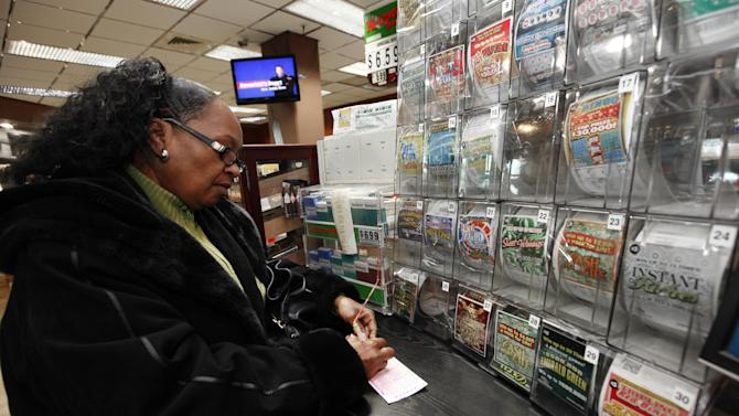 "Donna Fields picks her Powerball numbers in Detroit, Wednesday, Nov. 28, 2012. Fields picked two sets of numbers off the top of her head and two easy picks in tonight's Powerball total with an estimated 500 million dollar jackpot. Fields said, ""If I won I would take care of God first, then my family and do some traveling, and oh yeah, quit my job."" (AP Photo/Paul Sancya)"
