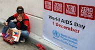 A vendor sits next to a world AIDS day poster displayed in front of the World Health Organization (WHO) regional office in Manila in 2011. Discrimination against homosexuals and people infected with HIV is contributing to the rapid rise of the incurable disease in the Philippines, officials and health activists said Friday