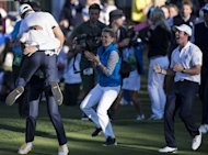 Team Europe&#39;s Martin Kaymer (top L) of Germany is embraced by Sergio Garcia of Spain as Rory McIlroy of Northern Ireland (R) cheers after winning the 18th hole to retain the Ryder Cup after a Singles Match on the final day of the 39th Ryder Cup at the Medinah Country Club in Medinah, Illinois