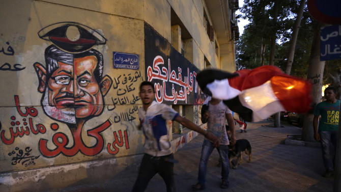 """Graffiti, including a caricature of President Mohammed Morsi, left and ousted President Hosni Munarak, is painted on the wall of a building across from the Ministry of Culture in Cairo, Egypt, Sunday, June 30, 2013. Hundreds of thousands of opponents of Egypt's Islamist president poured out onto the streets in Cairo and across much of the nation Sunday, launching an all-out push to force Mohammed Morsi from office on the one-year anniversary of his inauguration. Fears of violence were high, with Morsi's Islamist supporters vowing to defend him. The red Arabic words below the face drawing reads, """"Whoever cost it didn't die."""" The Arabic next to the face drawing reads, """"Down with the rule of sheep."""" The red and white Arabic reads, """"The revolution is everywhere against the killer and the traitor."""" (AP Photo/Hiro Komae)"""