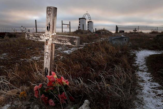 FILE - This Feb. 7, 2012 file photo shows a cross on a grave at the Wounded Knee National Historic landmark in South Dakota. Wednesday is the final day a landowner has given the Oglala Sioux Tribe to