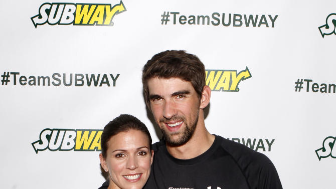 Whitney Phelps is joined by her bother, Olympic swimming champion Michael Phelps, as as she announces that she will run the ING New York City Marathon with Team SUBWAY at the Chelsea Piers Sport Center, Monday, Oct. 15, 2012 in New York. (Photo by Jason DeCrow/Invision for SUBWAY/AP Images)