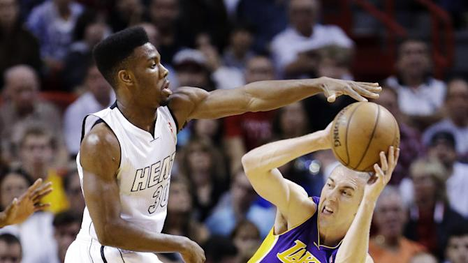 Los Angeles Lakers guard Steve Blake (5) looks for an open teammate past Miami Heat point guard Norris Cole during the first half of an NBA basketball game, Sunday, Feb. 10, 2013, in Miami. (AP Photo/Wilfredo Lee)