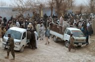 Afghan villagers load the bodies of those killed in a mass shooting allegedly by a US soldier in the village of Alkozai in Kandahar Province, March 11, 2012