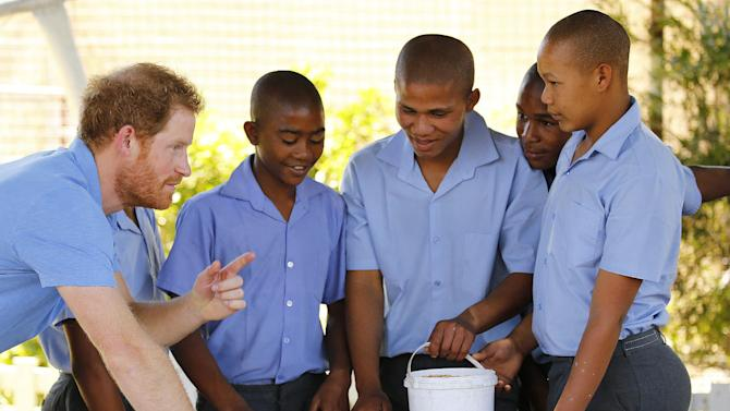 Britain's Prince Harry gestures as he talks with children during a visit to the Ottery Youth Care Centre in Cape Town