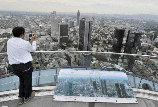 <p>A tourist takes a picture of the skyline of the banking district from the roof of a building in Frankfurt. France and Germany are bidding to revive a controversial financial transactions tax, seeking support from the European Commission and enough EU partners to start the tax in a core group.</p>