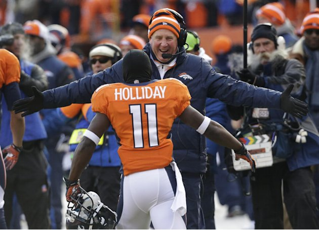 Denver Broncos wide receiver Trindon Holliday is greeted by Denver Broncos coach John Fox after running a punt return back 90 yards for a touch down against the Baltimore Ravens in the first quarter o