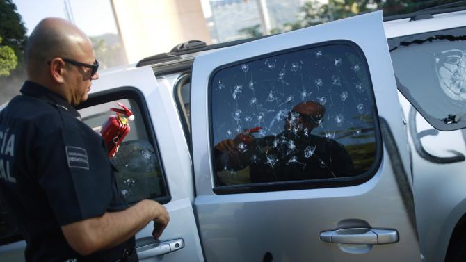 A federal police officer holds a fire extinguisher as he stands next to the vandalized vehicle of Acapulco's Mayor Luis Walton Aburto after a demonstration demanding justice for the 43 missing students from Ayotzinapa Teacher Training College, in Acapulco