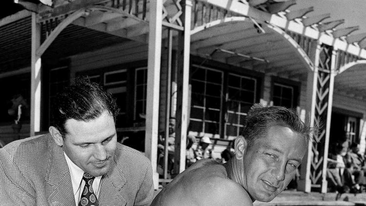 "FILE - In this Feb. 27, 1950 file photo, Philadelphia Phillies first baseman Eddie Waitkus, right, shows scars resulting from an operation following his shooting in Chicago in 1949, to his roommate, outfielder Bill Nicholson, on a beach in Clearwater, Fla. Waitkus was working his way back into condition at the team's spring training camp in Clearwater. Waitkus had been shot by 19-year-old Ruth Steinhagen at a hotel in one of the most sensational and bizarre criminal cases in Chicago history that made headlines around the country. Steinhagen died of natural causes at 83 in late December 2012. She was the inspiration for Bernard Malamud's novel ""The Natural"" and the 1984 movie starring Robert Redford, a mysterious woman who lured a major league ballplayer she'd never met into a hotel room with a cryptic note and shot him. (AP Photo/File)"