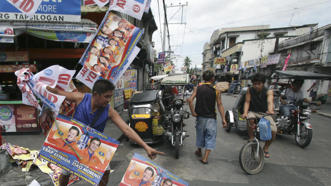 A man pulls down election posters of Manila Mayor Joseph Estrada and Vice Mayor Francisco Domagoso as he cleans the surroundings of a school used as a voting center during the mid-term elections in Manila, Philippines on Tuesday, May 14, 2013. Former President Joseph Estrada was proclaimed Tuesday as the new mayor of the Philippine capital, Manila, his first elected post since his ouster in an anti-corruption revolt 12 years earlier.(AP Photo/Aaron Favila)