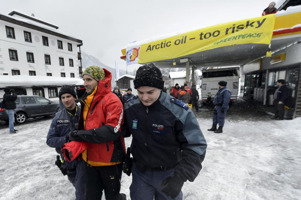 Police leads away a Greenpeace activist who was demonstrating in a Shell petrol station on the sideline of the 43rd annual meeting of the World Economic Forum, WEF, in Wolfgang near Davos, Switzerland, Friday, Jan. 25, 2013. (AP Photo/Keystone, Laurent Gillieron)