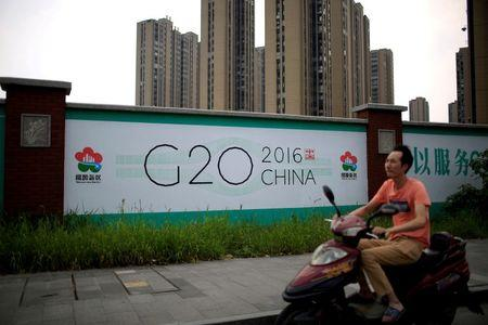 A man rides an electronic bike past a billboard for the upcoming G20 summit in Hangzhou