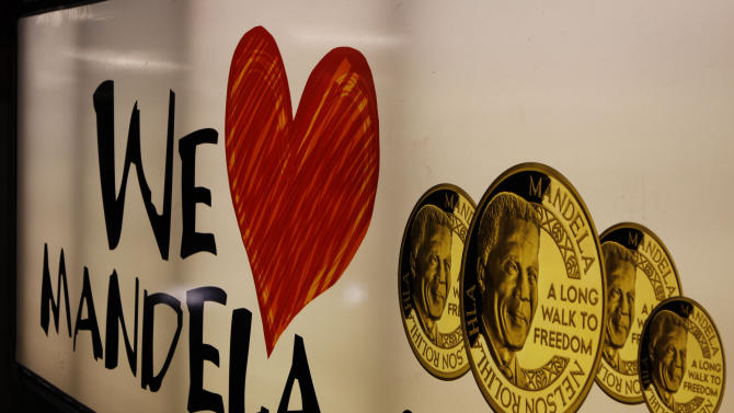 """A banner advertising gold coins with the image of  former South African President Nelson Mandela, in Johannesburg, Sunday Dec. 9, 2012. South Africans prayed Sunday for the health of former President Nelson Mandela and anxiously awaited further word about the anti-apartheid leader after he was admitted to a military hospital. President Jacob Zuma visited Mandela Sunday morning at the hospital in Pretoria and found the frail 94-year-old to be """"comfortable and in good care,"""" presidential spokesman Mac Maharaj said in a statement. Maharaj offered no other details about Mandela, nor what medical tests he had undergone since entering the hospital Saturday. (AP Photo/Denis Farrell)"""