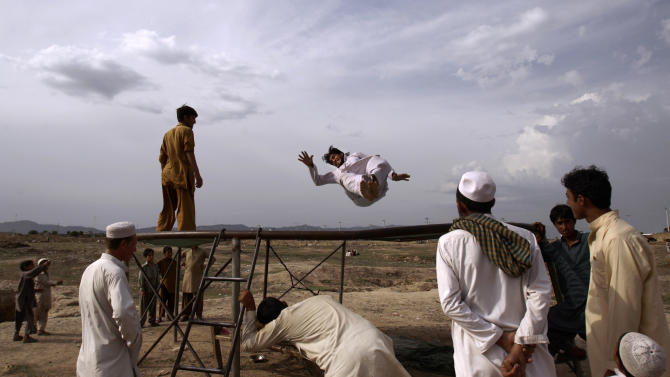 A Pakistani man who fled his village due to fighting between security forces and militants in Pakistan's tribal area of Bajur, enjoys jumping on a trampoline at a makeshift entertainment park set up in a slum area on the outskirts of Islamabad, Pakistan, Friday, May 11, 2012. (AP Photo/Muhammed Muheisen)