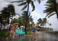 William Rath, Julie Rath, Laura Rath and Weera Rath, on vacation from the Netherlands, walk to the beach as they are buffeted by high winds of the outer bands of Hurricane Sandy in Miami Beach, Florida