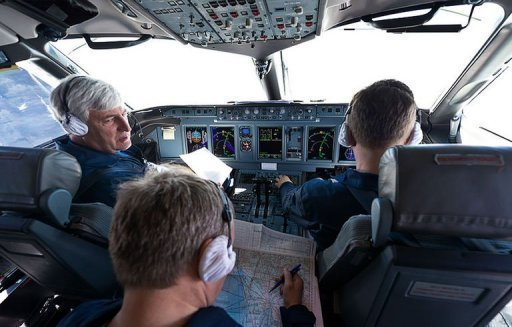 Russian Chief test pilot Alexander Yablontsev (L) in the cockpit of his Sukhoi Superjet 100 in Indonesia on May 8