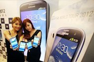 This photo, released by Samsung on June 25, shows South Korean models holding the company&#39;s latest smartphone, the Galaxy S3, during its unveiling ceremony for the domestic market in Seoul. Samsung Electronics, the world&#39;s largest smartphone maker, said it expects to have sold 10 million of its Galaxy S3 model by the end of July, two months after its launch