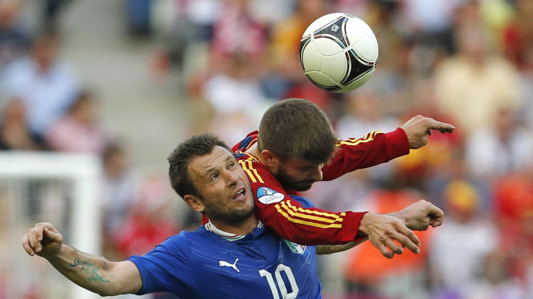 Italy's Antonio Cassano, left, and Spain's Gerard Pique go for a header during the Euro 2012 soccer championship Group C match between  Spain and Italy in Gdansk, Poland, Sunday, June 10, 2012. (AP Photo/Gregorio Borgia)