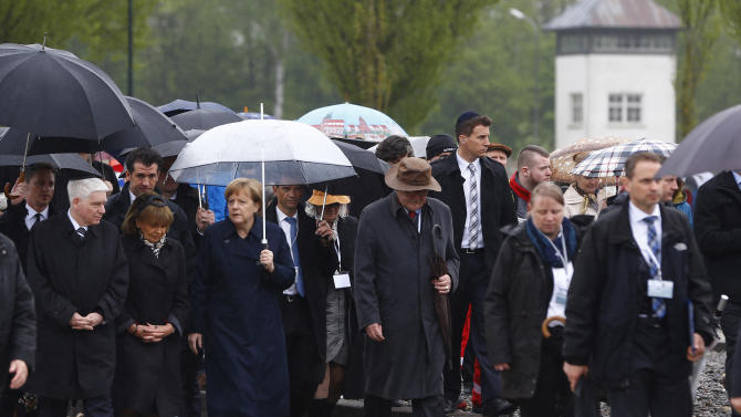 German Chancellor Angela Merkel, center, visits the memorial site for the former Nazi concentration camp in Dachau, southern Germany, Sunday, May 3, 2015 during an event to commemorate the 70th anniversary of the liberation of the camp. (AP Photo/Matthias Schrader