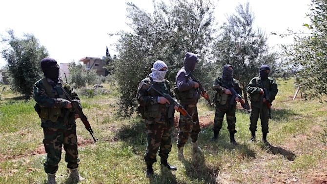 Members of the Lebanese pro-Syrian Popular Committees stand on the Lebanon-Syria border, Lebanon, Friday, April 12, 2013. The Popular Committees are backed by the Shiite Lebanese Hezbollah militant group, staunch supporters of Syrian President Bashar Assad who have been accused by rebels of fighting alongside the regime and launching attacks targeting rebels from inside Lebanese territory. The committees say they are defending Syrian villages across the border that are inhabited by Lebanese Shiite Muslims, who say they were attacked by rebels. (AP Photo/Bilal Hussein)