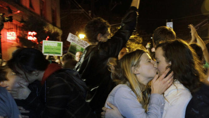 Revelers kiss as they celebrate early election returns favoring Washington state Referendum 74, which would legalize gay marriage, during a large impromptu street gathering in Seattle's Capitol Hill neighborhood, in the early hours of Wednesday, Nov. 7, 2012. The re-election of President Barack Obama and Referendum 74 drew the most supporters to the streets. (AP Photo/Ted S. Warren)