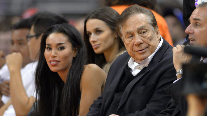 """In this photo taken on Friday, Oct. 25, 2013, Los Angeles Clippers owner Donald Sterling, right, and V. Stiviano, left, watch the Clippers play the Sacramento Kings during the first half of an NBA basketball game in Los Angeles. The NBA is investigating a report of an audio recording in which a man purported to be Sterling makes racist remarks while speaking to Stiviano. NBA spokesman Mike Bass said in a statement Saturday, April 26, 2014, that the league is in the process of authenticating the validity of the recording posted on TMZ's website. Bass called the comments """"disturbing and offensive."""" (AP Photo/Mark J. Terrill)"""