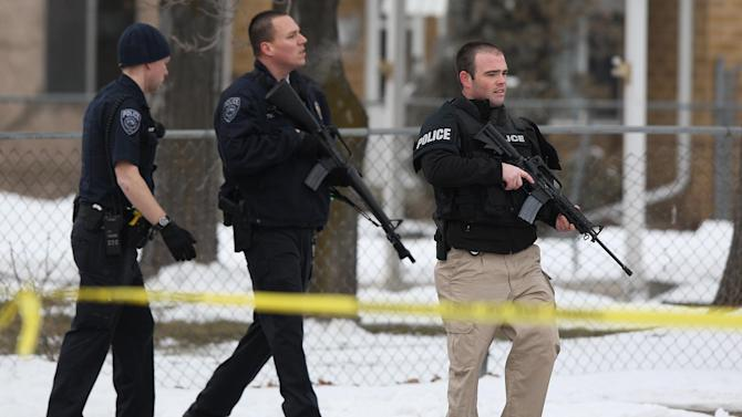 "Unified Police Department officers patrol a Midvale, Utah neighborhood after a shooting,  Tuesday, Feb. 12, 2013. Three people were shot to death and one was critically wounded at a known drug house in suburban Salt Lake City, causing temporary lockdowns at several area schools as police looked for two men who may have been involved. Investigators said a person inside the house reported the shooting in Midvale at about 8 a.m. Unified Police Department Lt. Justin Hoyal said a search warrant had been served at the house in recent weeks for drug activity. ""It was a known narcotics house,"" he said. (AP Photo/The Deseret News, Ravell Call)  SALT LAKE TRIBUNE OUT;  MAGS OUT"