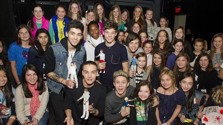 "Worldwide musical sensation One Direction showcases their Hasbro dolls while greeting the winners of Nickelodeon's ""Your Moment with 1D"" sweepstakes at an exclusive fan event on Monday, Nov. 26, 2012 in New York. (Photo by Charles Sykes/Invision for Hasbro/AP Images)"