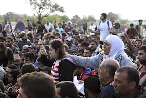 Refugees and migrants wait to pass the borders from…