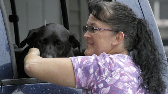 "Millie Brown, a cook and waitress at Buch's truck stop, right, pets ""Star"" a Labrador Retriever that belongs to one of her customers, after her shift, Thursday, Sept. 27, 2012, in Steubenville, Ohio. To look at Ohio is to glimpse America in a nutshell — a state full of places where laborers, truck drivers, cooks, store clerks and business owners form the backbone of small-town life. Places where the deli cashes checks, cars and trucks are ""vehicles"" and the NFL takes a back seat to high-school football .(AP Photo/Keith Srakocic)"