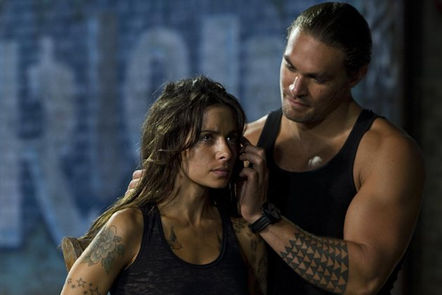 "This film image released by Warner Bros. Pictures shows Sarah Shahi, left, and Jason Momoa in a scene from ""Bullet to the Head."" (AP Photo/Warner Bros. Pictures, Frank Masi)"