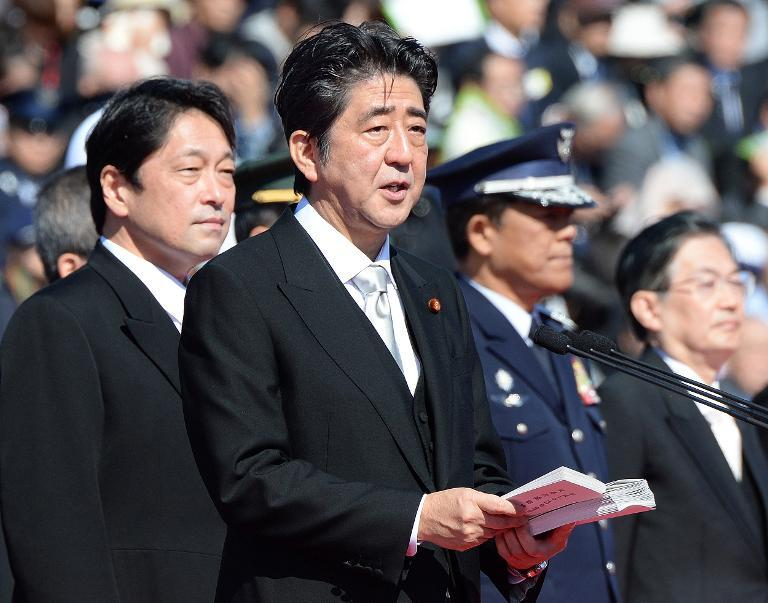 Japanese Prime Minister Shinzo Abe (C) delivers a speech next to Defence Minister Itsunori Onodera (L) during military review at the Ground Self-Defence Force's Asaka training ground, on October 27, 2013