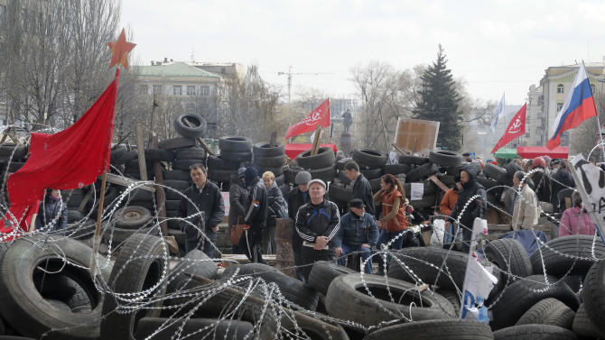 People stand at a barricade at the regional administration building that they had seized earlier in Donetsk, Ukraine, Tuesday, April 15, 2014. Several government buildings have fallen to mobs of Moscow loyalists in recent days as unrest spreads across the east of the country. (AP Photo/Efrem Lukatsky)