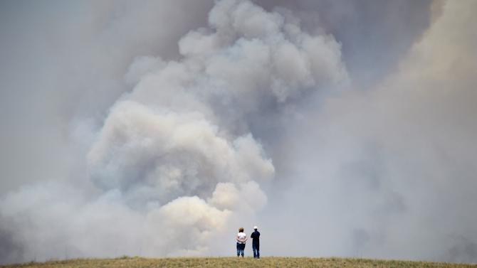 Chris and Christine Walker watch the Black Forest Fire gain steam as it burns out of control for a second straight day near Colorado Springs, Colo. on Wednesday, June 12, 2013. The Walkers live nearby and were under pre-evacuation orders. Three Colorado wildfires fueled by hot temperatures, gusty winds and thick, bone-dry forests have together burned dozens of homes and led to the evacuation of more than 7,000 residents and nearly 1,000 inmates at medium-security prison. (AP Photo/Bryan Oller)