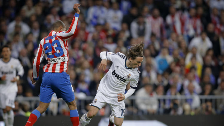 Atletico de Madrid's Miranda, left, duels for the ball with Real Madrid's Luka Modric from Croatia during the Copa del Rey final soccer match at the Santiago Bernabeu stadium in Madrid, Spain, Friday, May 17, 2013. (AP Photo/Daniel Ochoa de Olza)