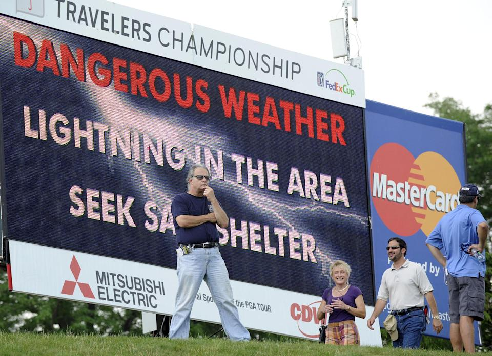 An unidentified spectator reacts to the announcement of a weather delay during the second round of the Travelers Championship golf tournament in Cromwell, Conn., Friday, June 22, 2012. (AP Photo/Fred Beckham)