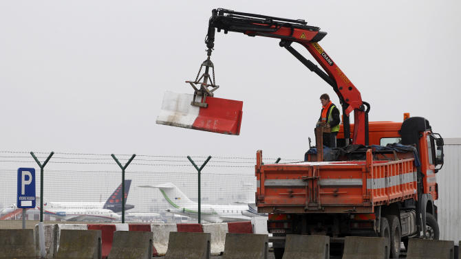 Workers place concrete blocks to block access to a security fence next to the tarmac, at Brussels international airport, Tuesday, Feb. 19, 2013. Eight masked gunmen made a hole in a security fence at Brussels' international airport, drove onto the tarmac and snatched some $50 million worth of diamonds from the hold of a Swiss-bound plane without firing a shot, authorities said Tuesday. (AP Photo/Yves Logghe)
