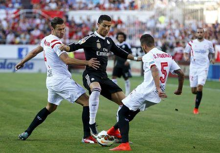 Real MadridÕs Cristiano Ronaldo is challenged by Sevilla's Grzegorz Krychowiak and Diogo Gomes Figueiras during their soccer match in Seville