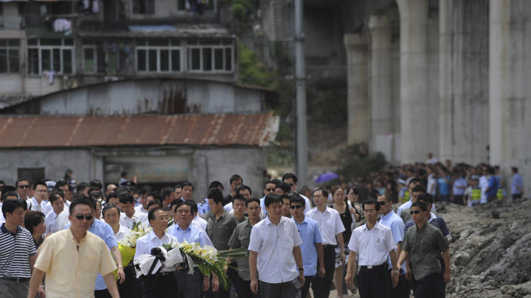 Chinese Premier Wen Jiabao holds a bouquet of flowers as he visits the site of the Saturday July 23, 2011 train crash, in Wenzhou, east China's Zhejiang province, Thursday, July 28, 2011. Wen vowed Thursday to punish anyone involved if there was corruption that caused the high-speed train crash that killed more than 35 people, amid growing public resentment of the handling of the accident. (AP Photo) CHINA OUT