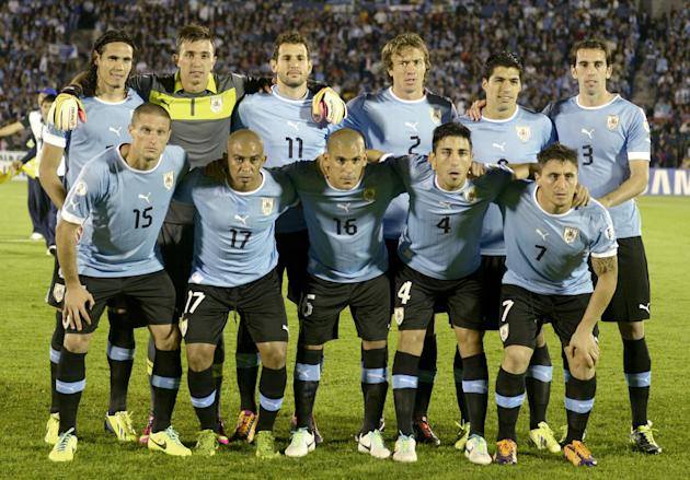 In this Oct. 15, 2013 file photo, Uruguay soccer team poses prior to the start the 2014 World Cup qualifying soccer match between Uruguay and Argentina in Montevideo, Uruguay. Foreground from left: Di
