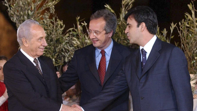 FILE - In this May 11, 2002 file photo Palestinian leader Yasser Arafat's economic adviser Mohammed Rashid, right, and Israeli Foreign Minister at the time Shimon Peres, left, shake hands as Rome's mayor Walter Veltroni looks on at a ceremony before the start of a concert in Rome's Colosseum. Rashid is being sought on suspicion he stole millions of dollars in public funds, the top Palestinian anti-corruption campaigner said Wednesday, May 16, 2012. (AP Photo/Gregorio Borgia, File)