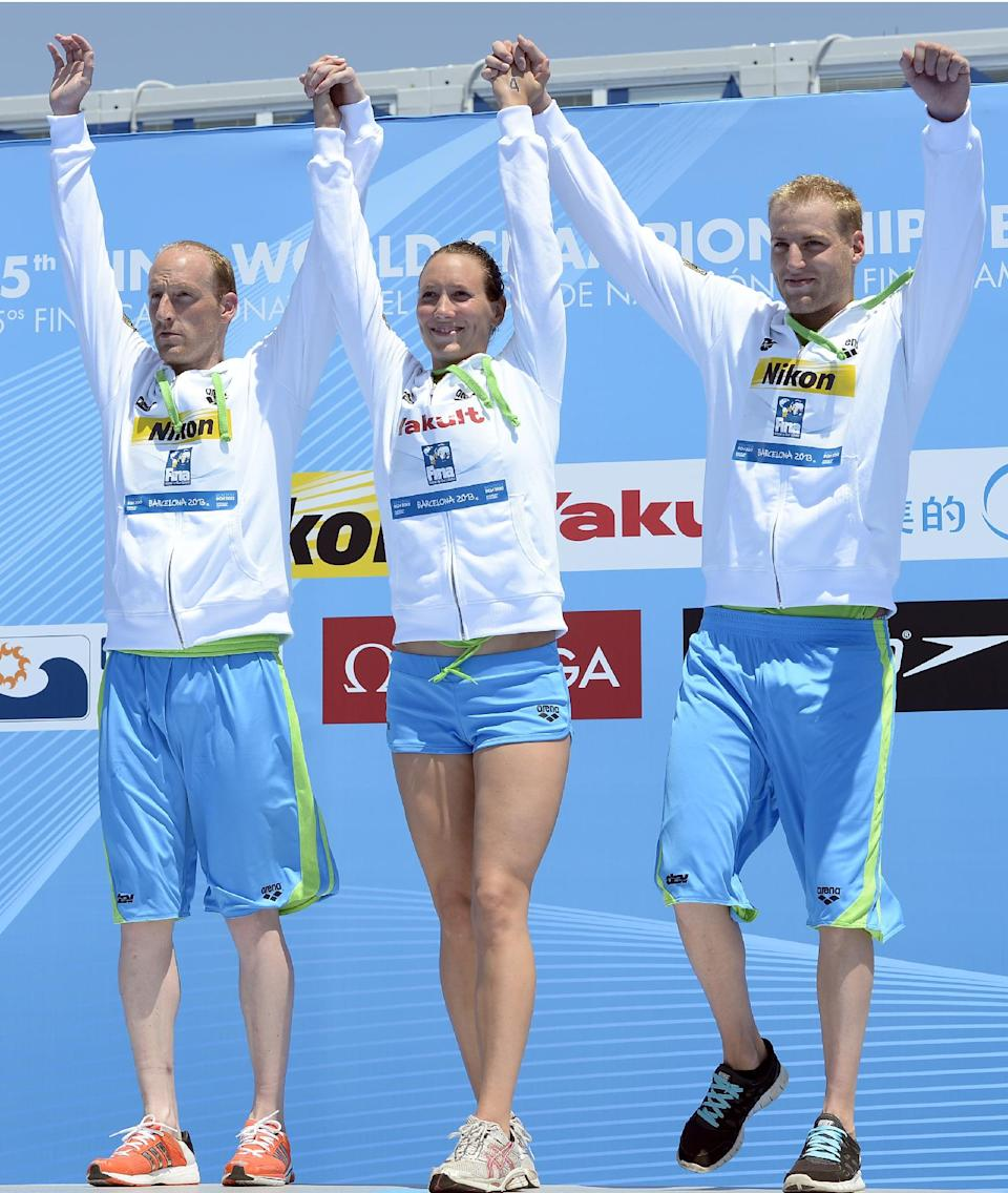 Gold medalists from Germany, from left, Thomas Lurz, Isabelle Harle, and Christian Reichert, right, celebrate as they stand on the podium following their win in the 5km team event open water swim competition at the FINA Swimming World Championships in Barcelona, Spain, Thursday, July 25, 2013.(AP Photo/Manu Fernandez)