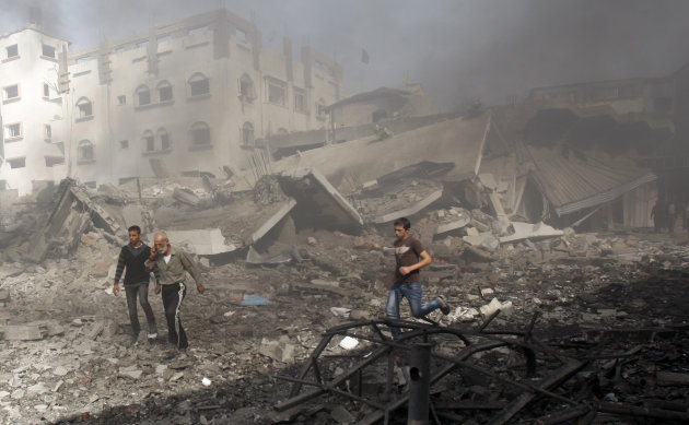 Palestinians hurry away from a damaged building after an Israeli air strike in Gaza City, Sunday, Nov. 18, 2012. Israel widened the range of targets in its Gaza offensive Sunday, striking more than a
